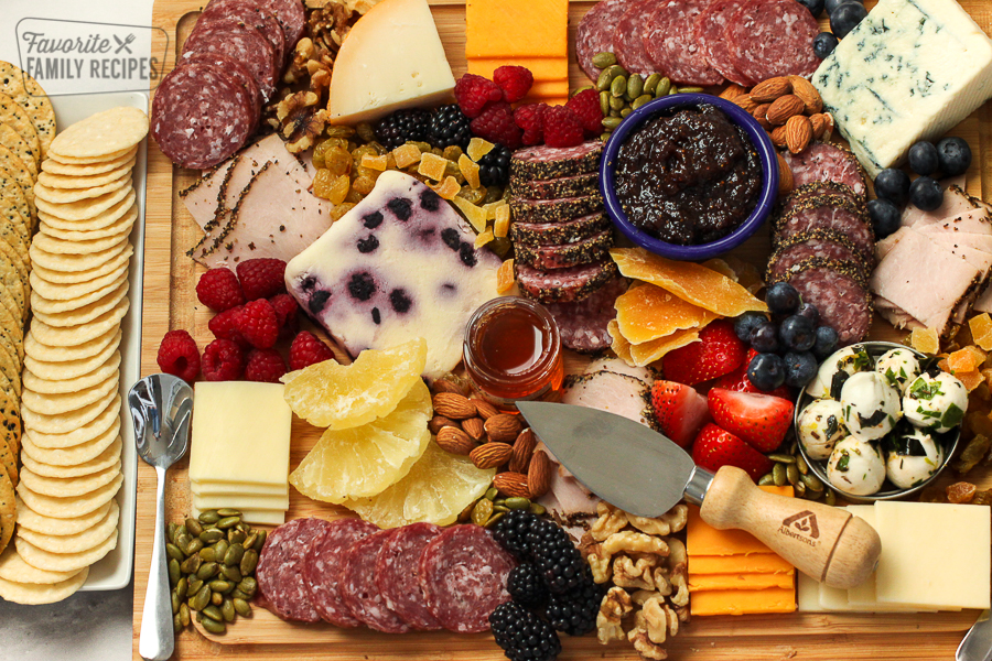 Charcuterie board with meats, cheeses, nuts, and dried fruit
