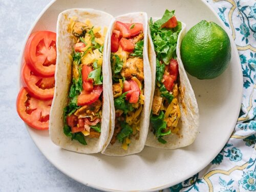 Three chicken tacos on a plate with sliced tomatoes and a lime on the side