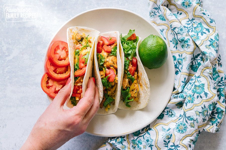 A hand reaching for one of three chicken tacos on a plate
