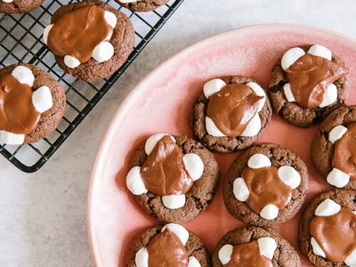 Chocolate marshmallow cookies on a cooling rack with a plate of cookies to the side