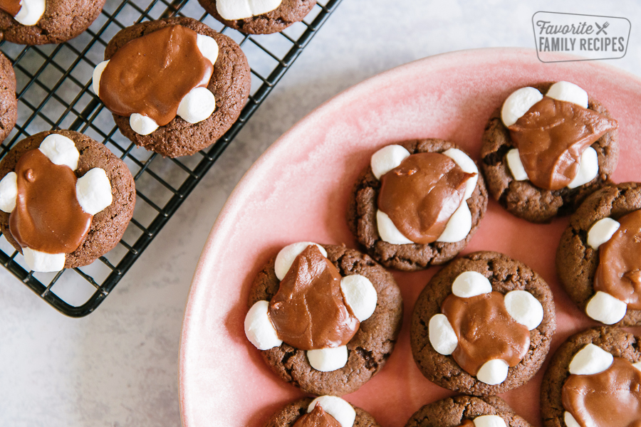 A pink plate filled with chocolate marshmallow cookies and a cooling rack with more cookies on the side