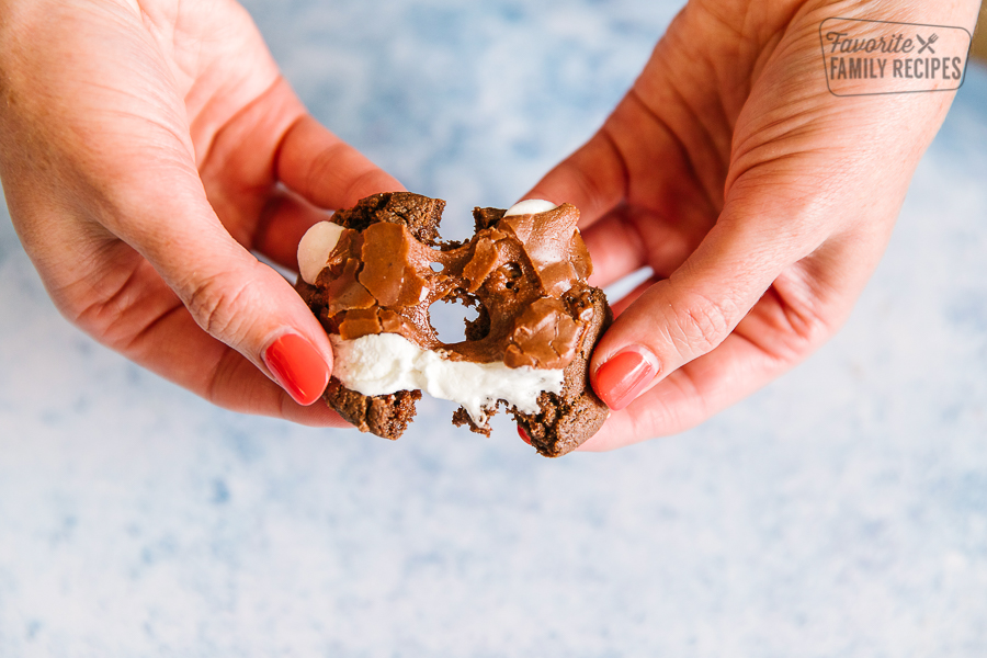 A chocolate marshmallow cookie being pulled apart with gooey marshmallow in the center