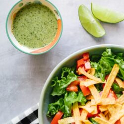 Cilantro Lime Dressing in a bowl with a salad and lime wedges on the side