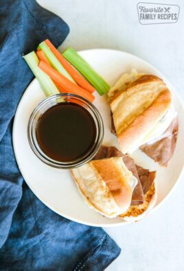 French Dip Sandwiches on a white plate with au jus and carrot and celery sticks