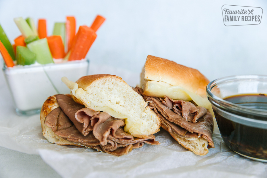 A French Dip sandwich cut in half with au jus and cut vegetables on the side