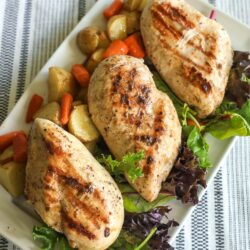 A tray of grilled chicken garnished with lettuce, red potatoes, and carrots