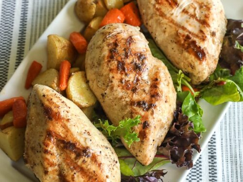 A tray of grilled lemon chicken garnished with lettuce, red potatoes, and carrots