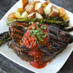 A grilled sirloin steak with tomato basil sauce on top and red potatoes on the side