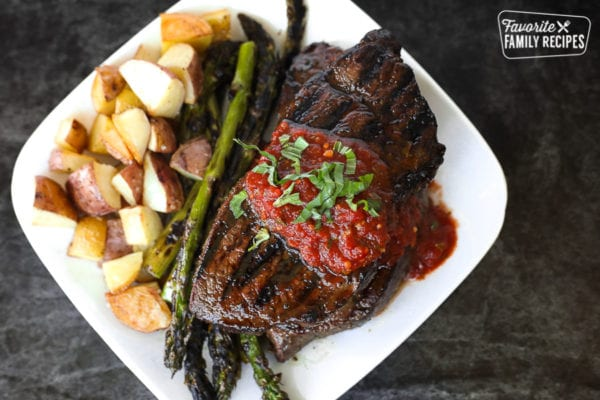 An overhead view of a sirloin steak with tomato basil sauce, asparagus, and roasted potatoes on the side