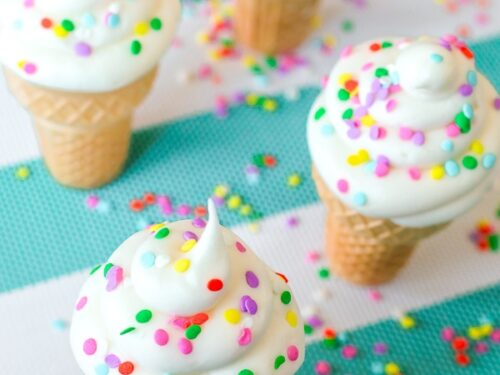 Four Ice Cream Cone Cupcakes on a teal and white striped tablecloth