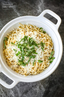 A white casserole dish filled with Mizithra Pasta topped with cheese and parsley