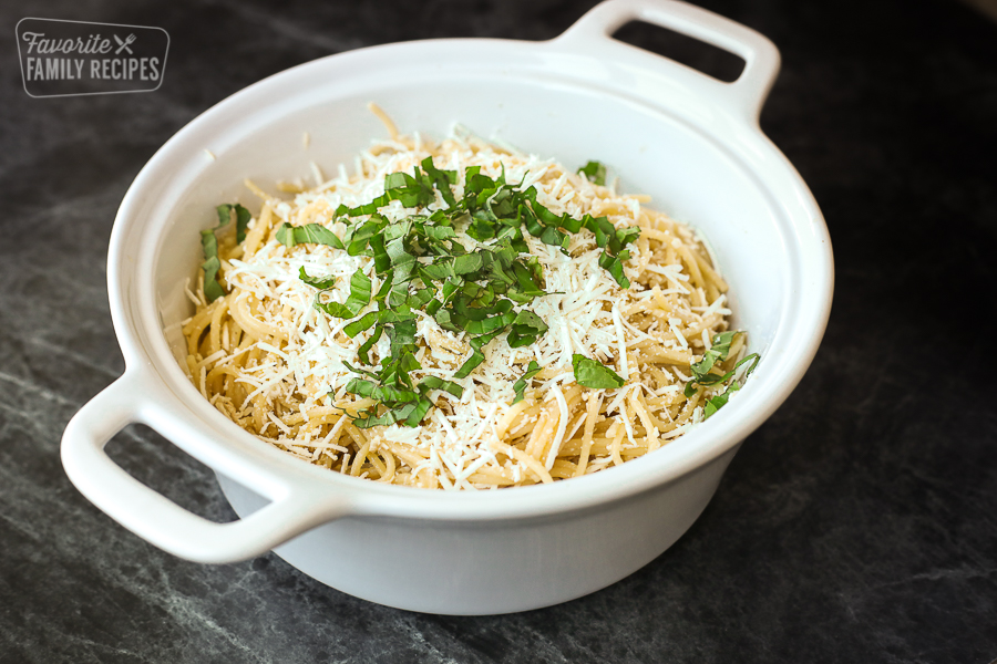 A landscape view of mizithra pasta sprinkled with mizithra cheese and basil on top