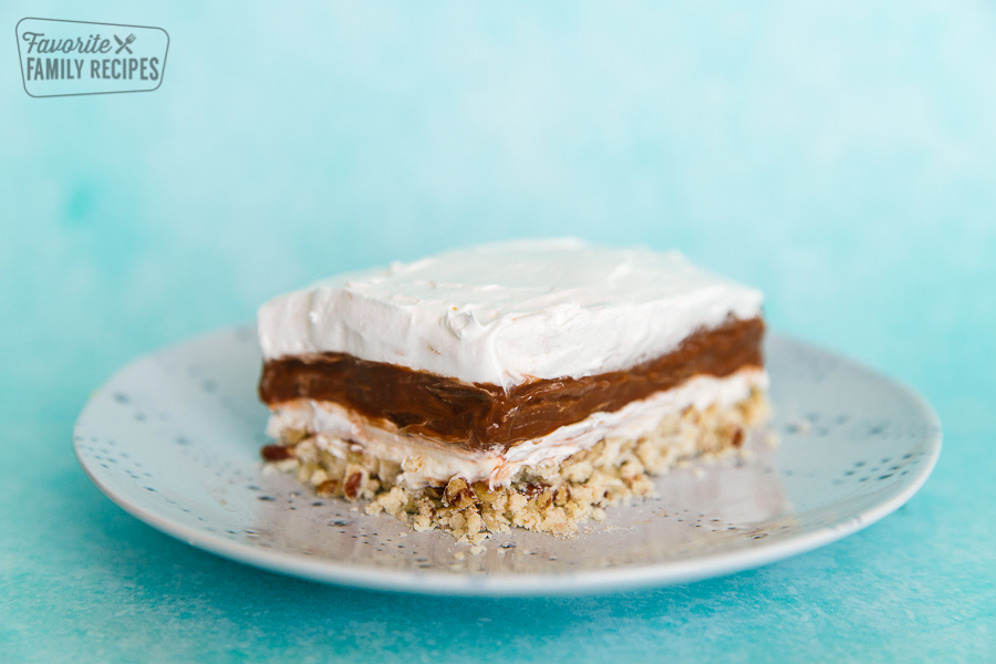 Side view of mud pie on a plate with layers of pudding, cream cheese, and cool whip
