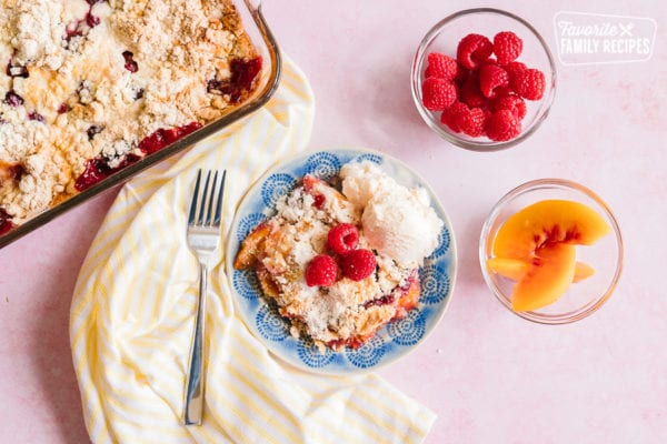 A serving of Raspberry Peach Cobbler on a blue plate with a casserole dish of cobbler on the side