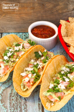 Three shrimp tacos with salsa and chips on the side