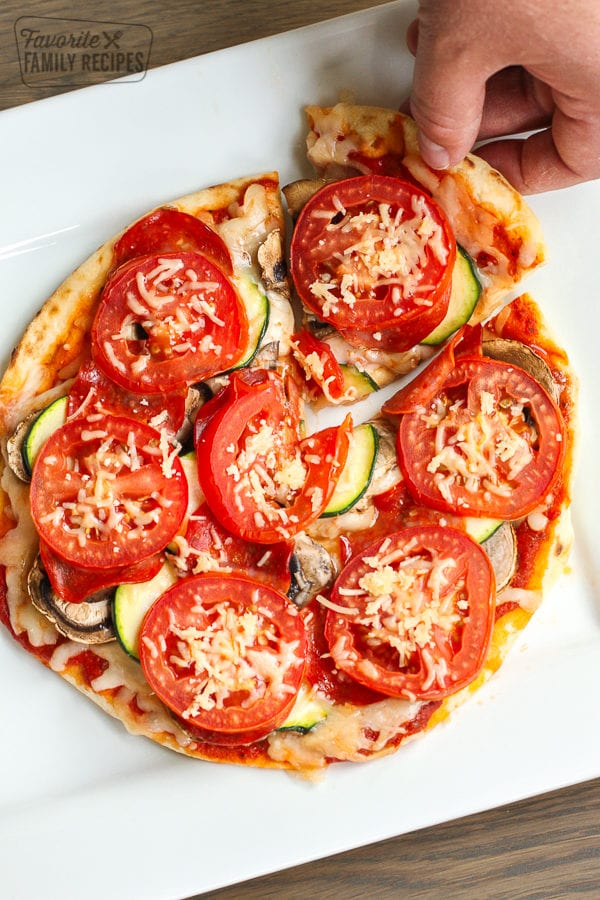 A healthy pizza with tomatoes and zucchini on a white plate