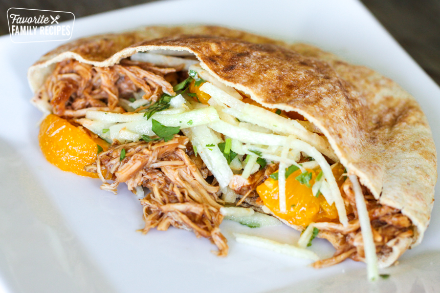 View of inside of a BBQ Chicken Pita with chicken, mandarin oranges, and jicama slaw