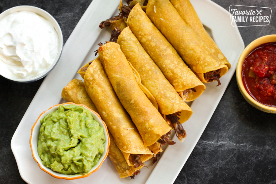 A platter of shredded beef taquitos with guacamole, sour cream, and salsa on the side