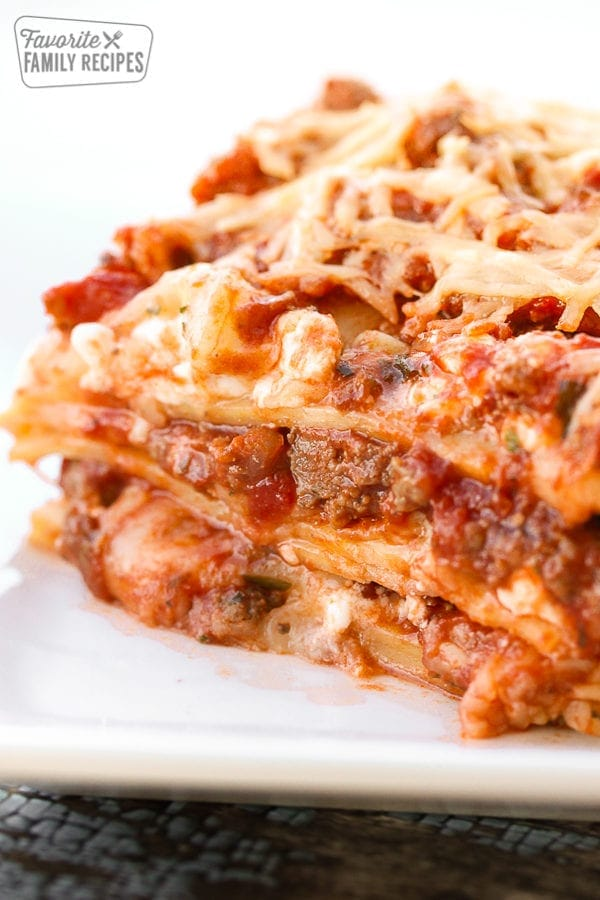 A piece of lasagna viewed close up with layers of lasagna noodles, meat, cheese, and tomatoes