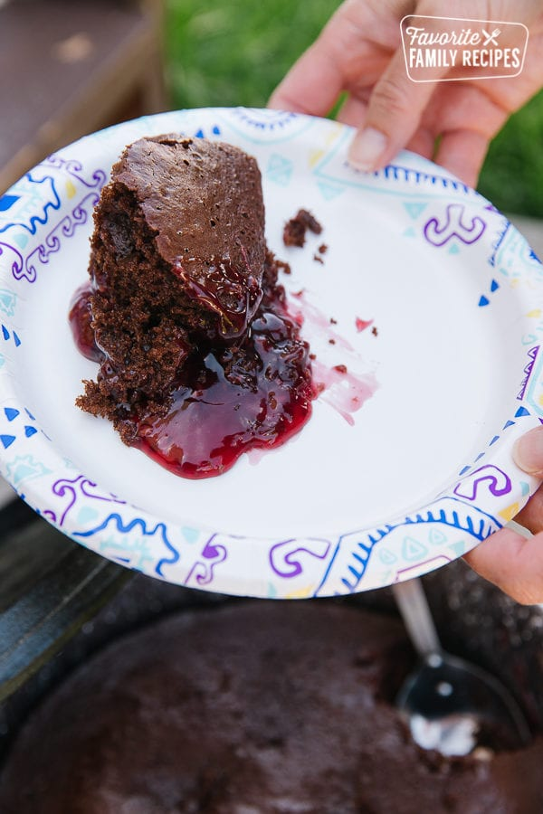A slice of chocolate raspberry cake served from a Dutch oven onto a paper plate