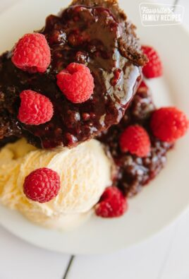 A serving of Chocolate Raspberry Cake with ice cream and raspberries as a garnish