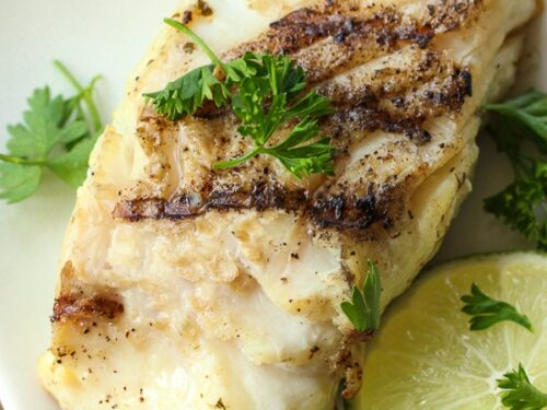 Grilled Cilantro Lime Halibut on a plate garnished with lime slices and cilantro