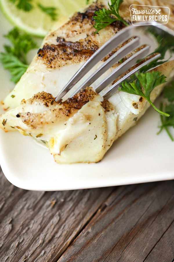 A fork cutting into a flaky piece of Cilantro Lime Halibut