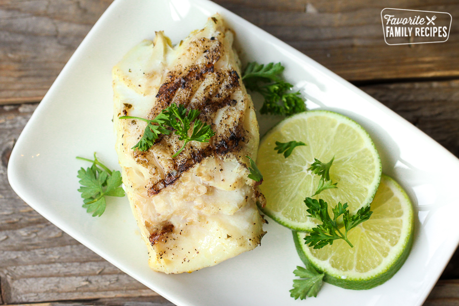 Cilantro Lime Halibut on a plate with lime slices and cilantro garnish on a plate