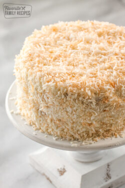 A round coconut cream cake on a cake platter