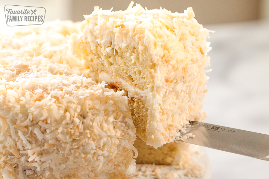 A slice of coconut cake being lifted from a cake platter