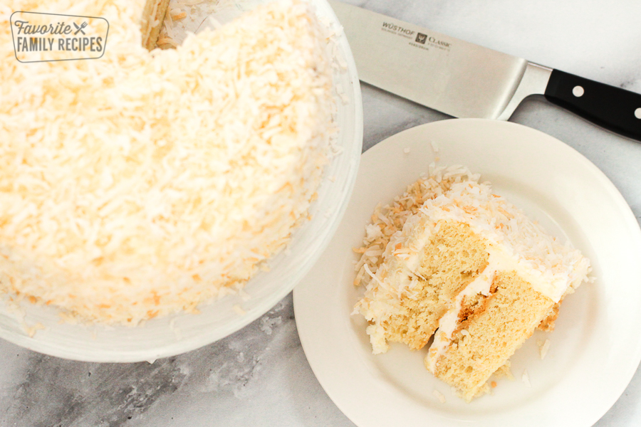 A slice of coconut cake on a plate with coconut cake in background