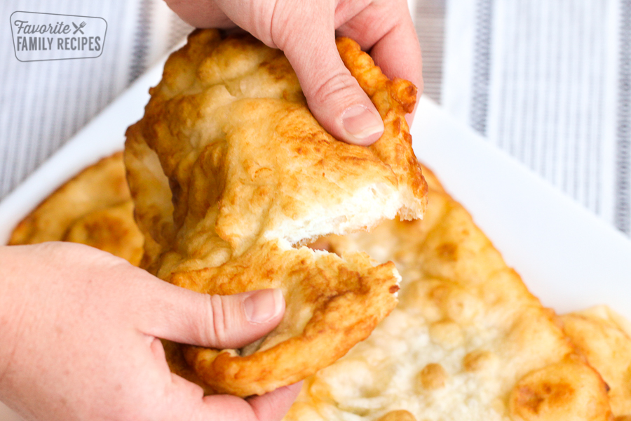 A piece of fry bread being pulled apart into two pieces