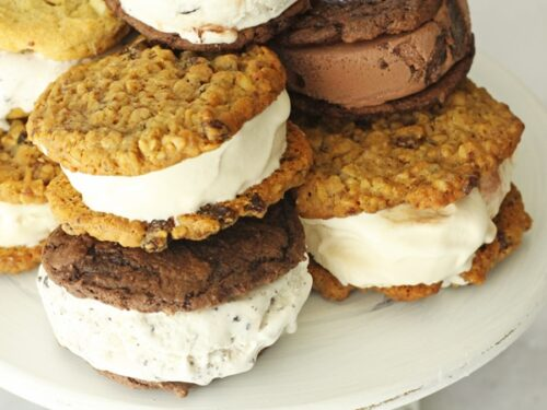 Six ice cream sandwiches stacked up on each other on a cake plate
