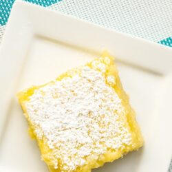 A square white plate with a lemon bar on it