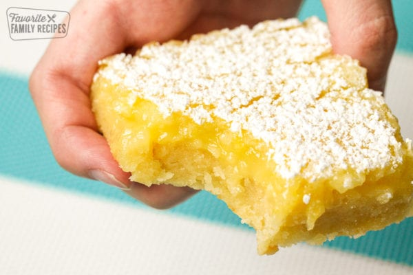 A Lemon Bar with a bite taken out of the middle