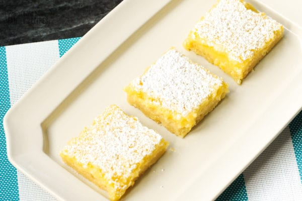 A white tray with three lemon bars in a row