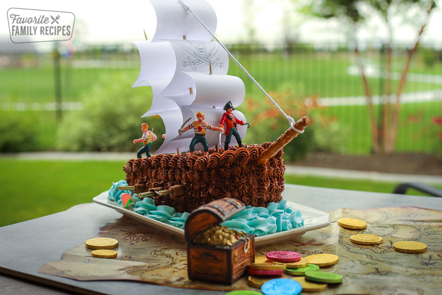 Pirate Ship Birthday cake on a pirate map surrounded by gold coins