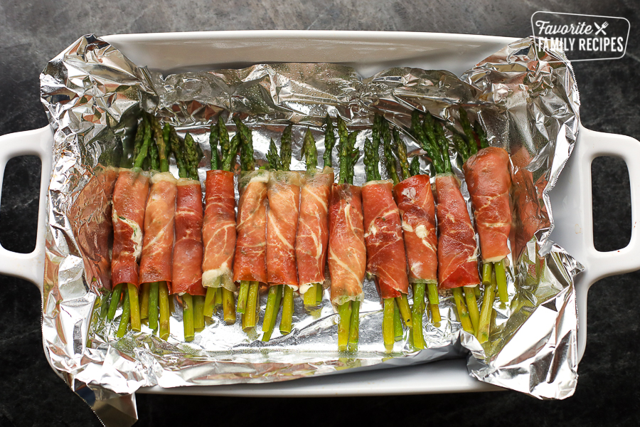 Asparagus wrapped in prosciutto being roasted in a pan