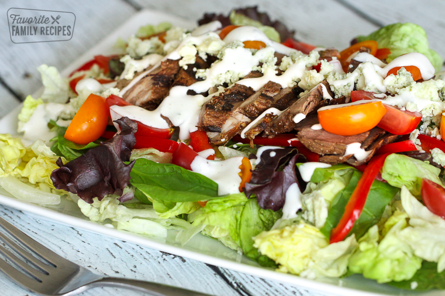 A bowl of steak salad with tomatoes, peppers, and bleu cheese dressing
