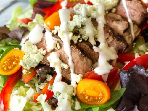 Steak salad with bleu cheese sprinkles and blue cheese dressing drizzled on top