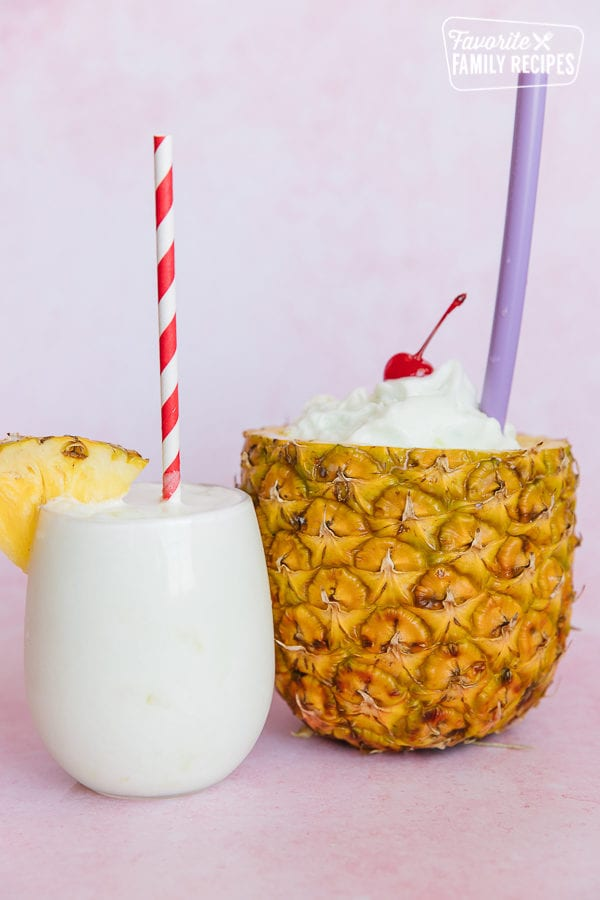 Two tropical slush drinks one served in a clear cup the other in a hollowed out pineapple
