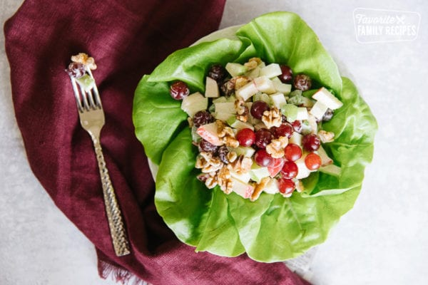 A Waldorf salad on a leaf of butter lettuce with a fork to the side
