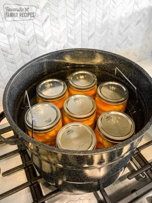 Glass jars filled with peaches in a water bath canner