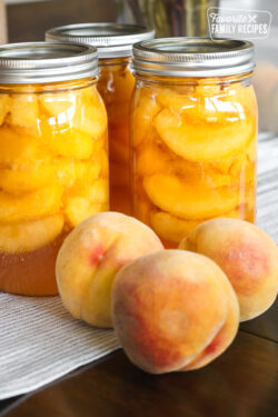 Home canned peaches in glass jars on a kitchen counter with fresh peaches on the side