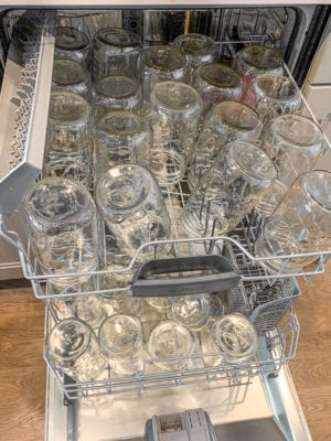Glass jars in the dishwasher to be sterilized for canning peaches
