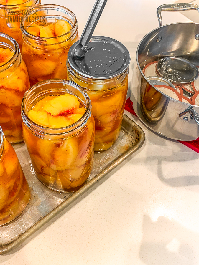 Lids being placed on glass jars filled with peaches for canning