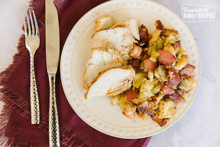 Thanksgiving stuffing with bacon on a plate with sliced turkey