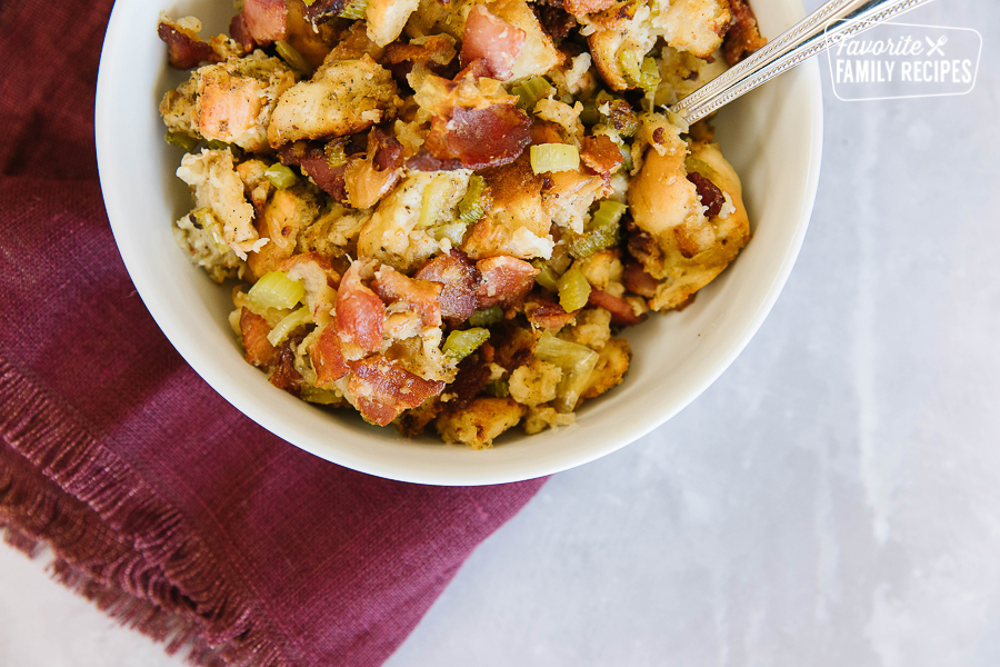 A bowl of Thanksgiving stuffing with bacon in a white serving bowl