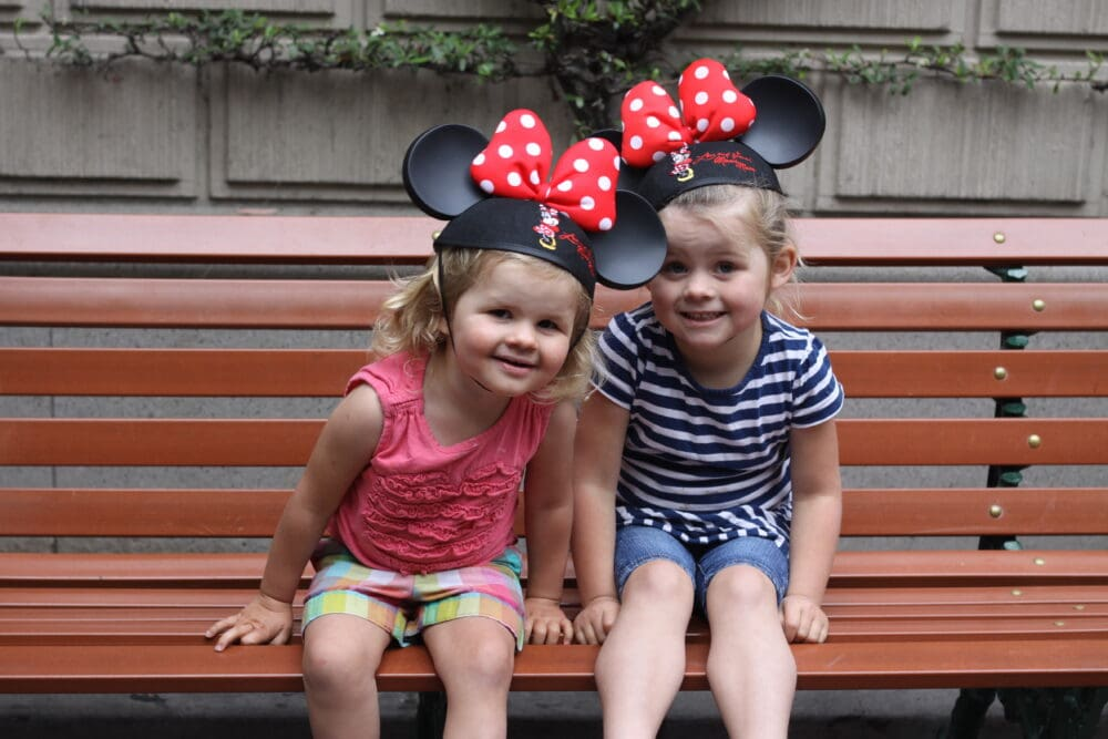 Two little girls with Minnie Ears sitting on a bench at Disneyland