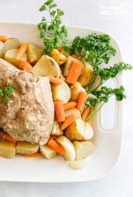 Crock Pot Pork Roast on a white tray with vegetables and a spray of parsley on the side